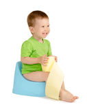 Boy sitting on a potty. Cute laughing baby boy with toilet paper sitting on a blue potty isolated on white background Stock Photos