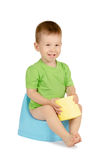 Boy sitting on a potty. Cute smiling baby boy with toilet paper sitting on a blue potty isolated on white background Royalty Free Stock Photography
