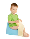 Boy sitting on a potty. Cute smiling baby boy with toilet paper sitting on a blue potty isolated on white background Royalty Free Stock Photos
