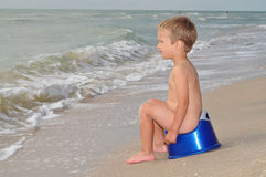 Boy sitting on a potty on the seashore. Lonely boy looks afar sitting on a chamber-pot. Freedom, childhood, immediacy stock photography