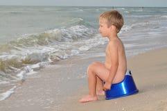 Boy sitting on a potty on the seashore Stock Photography