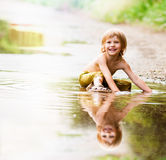 Boy sitting in puddle Stock Photos