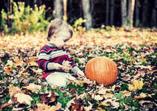 Boy Sitting Beside Pumpkin Looking Down - Vintage royalty free stock photo