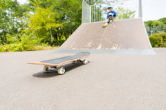 Boy Sitting on Ramp Looking Down at Skateboard Stock Images
