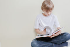 Boy sitting and reading a book at home. Education, school, leisure concept. Royalty Free Stock Images