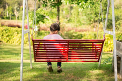 Boy sitting on the red seat swing in the park Royalty Free Stock Photos