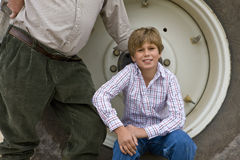 Boy sitting on rim of tractor wheel Royalty Free Stock Photo