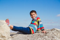 Boy sitting on a rock holding up his feet Stock Image