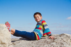 Boy sitting on a rock holding up his feet Stock Images