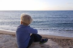 Boy sitting on rocks near sea shore waiting stock photo