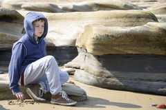 Boy sitting on rocks. Young boy in blue jacket sitting on rocks gazing into the distance at the seaside. Taken in Whitley Bay in North East England stock image