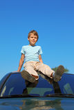 Boy sitting on roof of car Stock Image