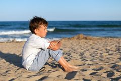 Boy sitting on sand at beach Royalty Free Stock Photos