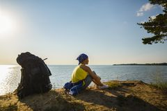 Boy sitting on sand cliff looking to sea. Travel and tourism concept Royalty Free Stock Images
