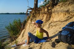 Boy sitting on sand cliff looking to sea. Travel and tourism concept Stock Image