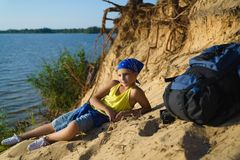 Boy sitting on sand cliff looking to sea. Travel and tourism concept Stock Photo