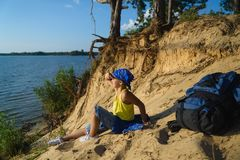 Boy sitting on sand cliff looking to sea. Travel and tourism concept Royalty Free Stock Photography