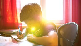 Boy sitting at school desk and does the job. School education. The sun`s rays through the glass. Boy sitting at school desk and does the job. School education stock video
