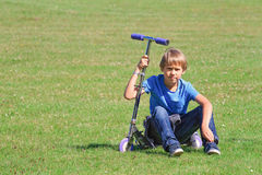 Boy sitting on a scooter in the park Royalty Free Stock Photography