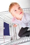 Boy is sitting in shoping basket and looking away Royalty Free Stock Photography