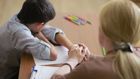 Boy sitting in silence during session with young psychologist. holding the hand stock video