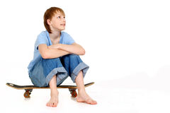 Boy sitting on skateboard Stock Photo