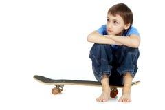 Boy sitting on skateboard Royalty Free Stock Photos