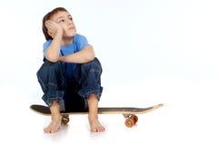 Boy sitting on skateboard Royalty Free Stock Images