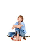 Boy sitting on skateboard Stock Photo