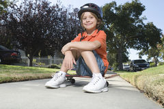 Boy Sitting On Skateboard Outdoors Stock Photo