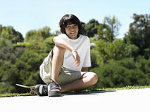 Boy (10-12) sitting on skateboard in park, smiling, portrait Stock Photo