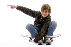 Boy sitting on skateboard and pointing Royalty Free Stock Photography