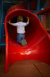 Boy is sitting at the slide hole Royalty Free Stock Images