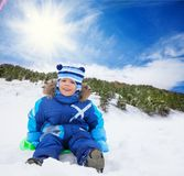 Boy sitting in snow on sled Stock Photography