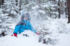 Boy is sitting in snow, winter forest Stock Photos