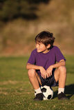 Boy sitting on soccer ball Stock Images
