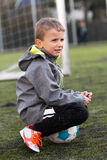 Boy Sitting on Soccer Ball Royalty Free Stock Photo