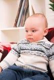Boy sitting on sofa Stock Images