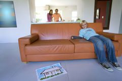 Boy(6-8) sitting on sofa, couple embracing in background, smiling, portrait Royalty Free Stock Photos