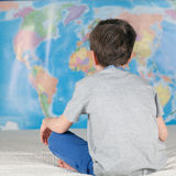 Boy sitting on sofa and studying map of world Stock Photography