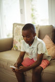 Boy sitting on sofa and using mobile phone in living room Royalty Free Stock Images
