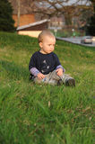Boy sitting on spring grass Stock Images