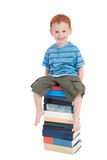Boy sitting on stack of books Stock Photos
