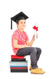 Boy sitting on stack of books and holding diploma Royalty Free Stock Image