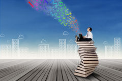 Boy sitting on stack of books with laptop Stock Photos