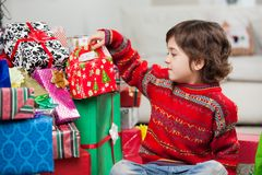 Boy Sitting By Stacked Christmas Gifts Royalty Free Stock Image