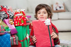 Boy Sitting By Stacked Christmas Presents Stock Image