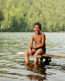 Boy sitting on stage. Asian boy sitting on stage in lake portrait stock photo