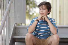 Boy sitting on the stairs Stock Image