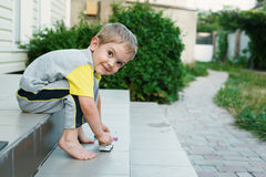 Boy sitting on stairs in back of  his house smiling Stock Photo